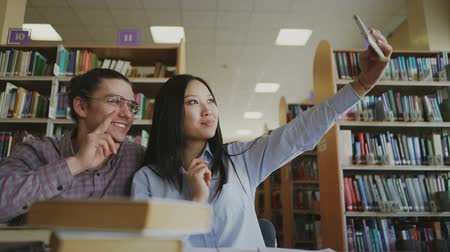 self examination : Young teenage couple of students sitting at table in library surrounded by books getting ready for exam. Girl is holding her smartpone and taking selfie with her classmate Stock Footage
