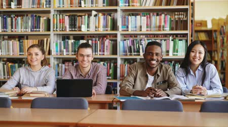 higher : Portrait of four multi-ethnic students sitting at long desk in big spacious library with piles of books looking at camera and smiling positively