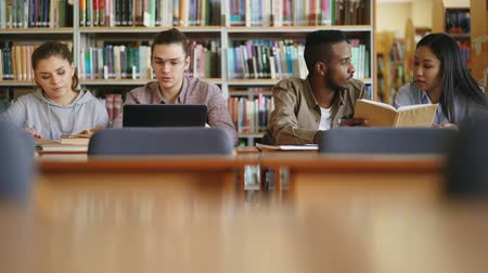 одноклассник : Multi-ethnic group of students siting in library with books and laptop on table getting ready for examination together smiling and laughing Стоковые видеозаписи