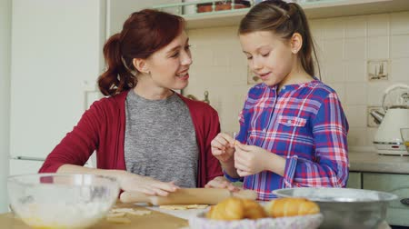 coming home : Cheerful mother cooking in the kitchen while cute daughter coming and embracing mom in the morning. Family, food, home and people concept