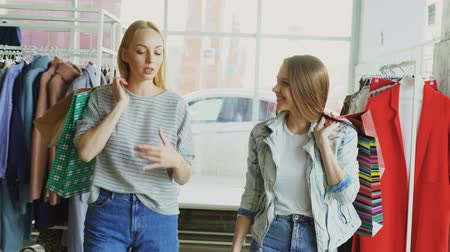 moda : Dolly shot of two girls walking slowly through spacious shop with colourful paper bags. One of them is speaking emotionally, the other one is listening and smiling.