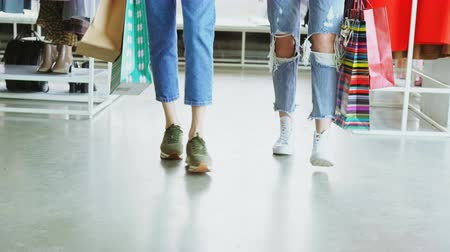 потребитель : Close-up dolly shot of womens legs walking slowly through luxurious shop. Women are wearing jeans and trainers and carrying bright paper bags.