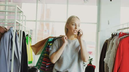 шопоголика : Attractive blond woman is walking between shelves and rails in large store and talking on mobile phone. She is carrying bags, smiling and looking at trendy clothes around her. Стоковые видеозаписи