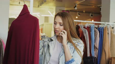 svetr : Young woman talking on mobile phone and choosing clothes in boutique. She is looking at knitted jumper, touching it and smiling.
