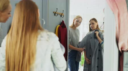 appraising : Pretty young woman is checking fashionable coat in fitting room with her friend helping her to appraise garment. They are talking, gesturing and looking at clothing.