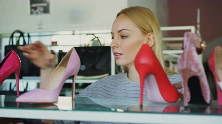 pięta : Close-up shot of blond young woman choosing high-heel shoes in footwear store. She is examining different heels carefully and smiling.
