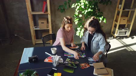 предпринимателей : High angle view of young designers are placing photos on table to create perfect flat lay working at studio. They are sitting at table together and discussing different photos Стоковые видеозаписи