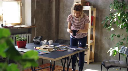 kolaż : Young creative girl is making flat lay out of colorful photos, then shooting them with camera. Woman is standing near modern table and wearing casual clothes. Wideo