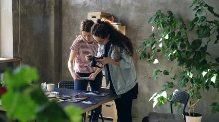 editor : Young female enterpreneurs are placing photos on table to make flat lay and shooting with camera while standing in modern office. Women are sharing ideas and discussing design. Stock Footage