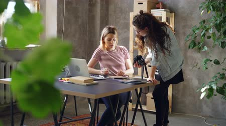 ilustrar : Young professional designer is discussing new project with female photographer, watching photos on camera, choosing illustrations carefully. Stock Footage