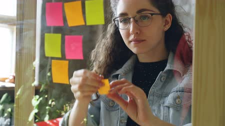 çıkartmalar : Close-up of young attractive woman wearing glasses sticking colored memos on glass board in modern office. She is looking at bright notes and smiling. Stok Video