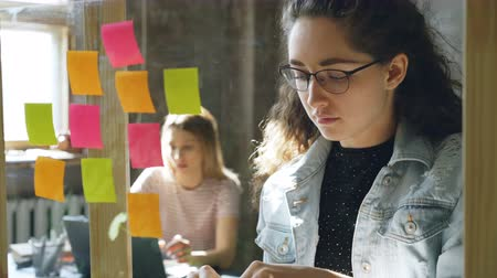 papírnictví : Close-up shot of attractive young businesswoman standing and sticking colourful memos on glass board. Her colleague is sitting and working in background. Creative work concept. Dostupné videozáznamy