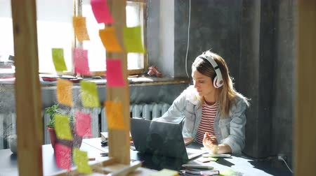 одиноко : Pretty blond girl is listening to music and working with laptop in nice loft office. She is making notes in notepad, smiling and dancing. Relaxing in workplace concept.