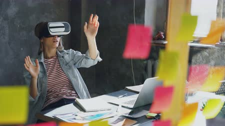 захватывающий : Attractive young woman is sitting at table and wearing virtual reality glasses. She is moving hands and and having VR experience in modern lof office