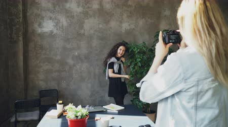 fotoğrafçı : Attractive girl is posing with large plant while female colleague photogrpahing her on digital camera in modern lof office. Women are having fun and laughing during coffee break Stok Video