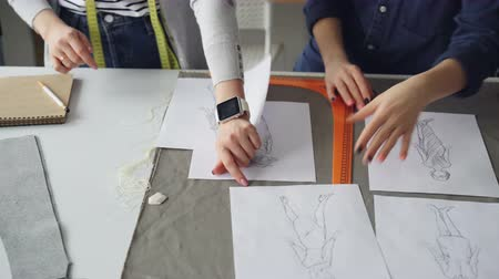 шитье дамского платья : Close-up shot of tailors hands going through sketches on sewing desk. Women are discussing clothing designs. Creative dressmakers work concept.