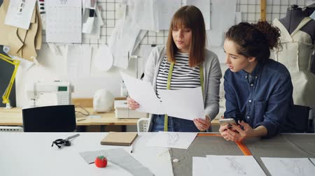 couturier : Young women working in design industry are comparing sketches and talking about them while working in modern tailor shop. Productive teamwork concept. Stock Footage