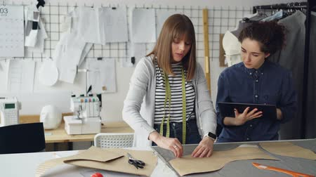 couturier : Female clothing designer is drawing outlines of new garment on fabric with chalk while her colleague is helping her and using tablet. Technologies in clothes manufacturing concept.