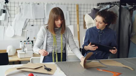 couturier : Young tailors are working with tablet, communicating and outlining clothing pattern on textile on studio desk. Light workshop with sewing items in background. Stock Footage