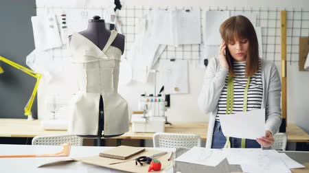 couturier : Self-employed seamstress is talking on mobile phone and looking through clothing sketches in her studio. Sewing items, dummy and drawings pinned on wall are visible.