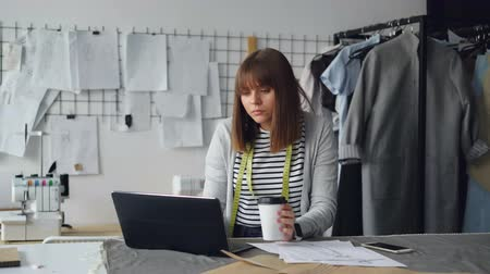 cansado : Young attractive seamstress is working with laptop and drinking coffee in her studio. She is having rest after work. Relaxation in workplace concept. Stock Footage