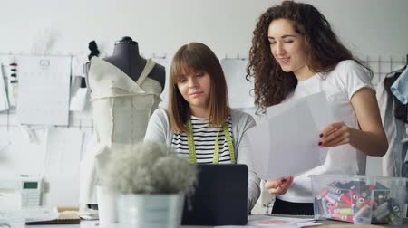 couturier : Owner of tailoring studio is working with laptop in workplace while her designer is coming to her with sketches. Women are looking at screen and drawings and discussing clothes.