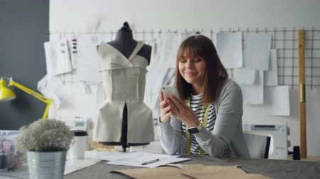 couturier : Professional clothing designer is sketching then receiving message on smartphone. She is taking device, touching screen and smiling, then proceeding with sketch.
