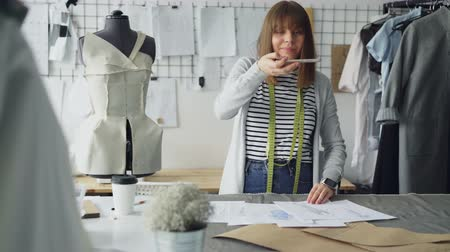 sharing : Ambitious creative female tailor is placing garment sketches on studio desk and shooting them with smartphone. Presenting drawings of new collection concept.