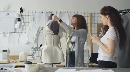 couturier : Young woman is measuring mannequin parts with tape-measure while her colleague is entering this information in smartphone. Productive cooperation in tailoring business concept.