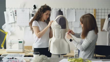 female measurements : Creative fashion designers are pinning cut out pieces of fabric to mannequin while sewing womens garment in modern studio. Ladies are concentrated on their work.