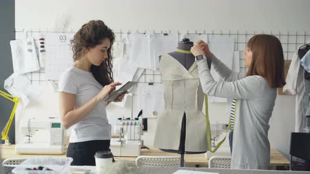 metrik : Clothing designer entrepreneurs are measuring mannequin parts while working in nice modern studio. Young attractive woman is using tablet to enter measurement results. Stok Video