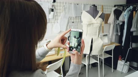 couturier : Young female clothing design blogger is shooting tailoring dummy with half-finished garment pinned to it. Close-up shot of girls hands and smartphone.