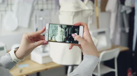 couturier : Close-up shot of womens hands holding smartphone and photographing tailoring dummy with half-finished garment pinned to it. Modern technologies in small business concept.