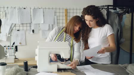 couture : Attractive dressmakers are looking at sketches and working with sewing machine, then checking stitches and adjusting equipment. Professional teamwork concept.