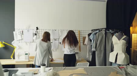 couturier : Young entrepreneurs clothing designers standing in front of wall with hanging sketches, discussing drawings and placing images with clips. Creative team working together concept.