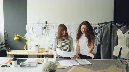 couturier : Young woman clothing desigher is drawing sketch when her coworker is coming to her with draft, showing and improving image and discussing it with colleague.