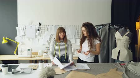 couturier : Young fashion designing entrepreneurs are discussing sketches of new clothes collection in their light studio. Women are looking through drawings, gesturing and talking. Stock Footage