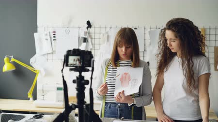 couturier : Young attractive vloggers clothing designers are recording video for their vlog. Women are showing garment sketches, gesturing and talking emotionally. Stock Footage