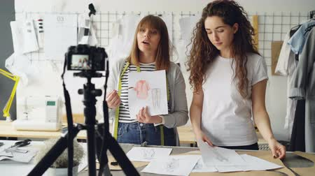 subscribers : Young women fashion bloggers recording video blog about ladiesclothes on camera and talking to followers in modern studio. Many garment sketches are visible.