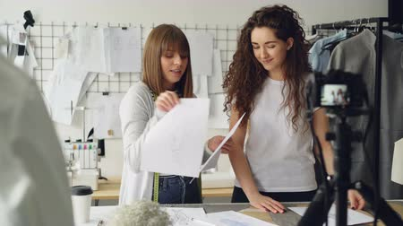 subscribers : Young pretty women fashion designers bloggers are recording video with camera about sewing new garment. Girls are showing sketches and templates and talking together. Stock Footage