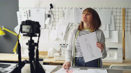 mass shooting : Creative blogger is recording video about her new garment collection using camera. She is showing sketch and talking about it emotionally for videoblog.