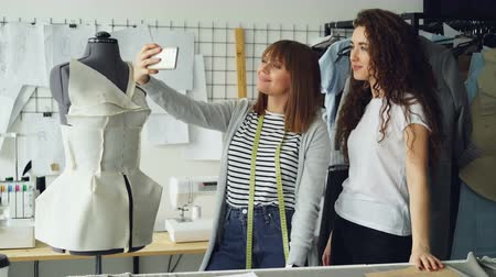 mass shooting : Two creative female designers are making selfie with smart phone while standing beside tailoring dummy in workplace. Attractive women are smiling and posing.