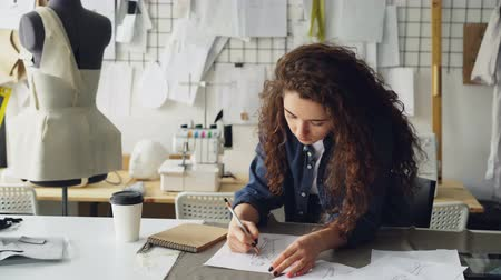 couturier : Young female artist fashion designer is drawing womens garment sketch at table in modern studio. Mannequin, sewing items, take-away coffee are visible.