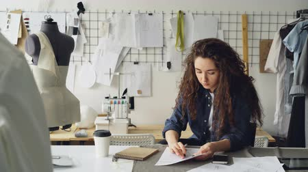 couturier : Young woman fashion designer is drawing ladies garment sketch at desk in modern workshop. Mannequin, sewing items, to-go coffee are visible.
