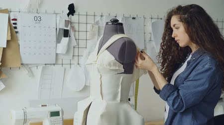 manekin : Young female tailor is adjusting clothes on tailoring dummy with sewing pins and measuring with measure-tape. Womens garments, sketches on wall, tailoring items are visible. Wideo