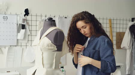 manequim : Young pretty seamstress is busy adjusting clothing on tailoring dummy with sewing pins. Womens garments, sketches on wall, tailoring tools are visible.