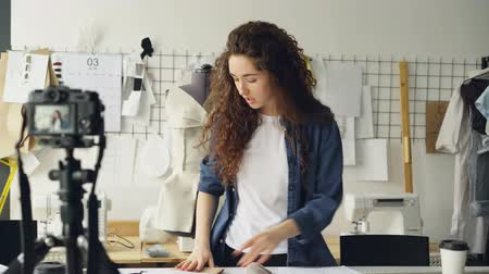 mass shooting : Young attractive seamstress fashion blogger is recording video with camera, talking and showing sketches and tailoring items. Blogging for successful startup concept. Stock Footage