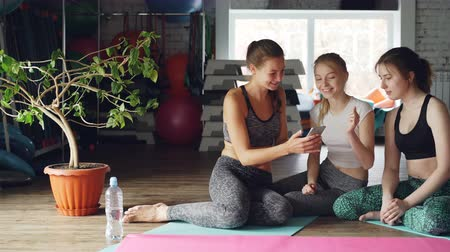 socialising : Young women are socialising watching smartphone in gym. They are touching screen, gesturing, chatting emotionally and laughing. Sports and modern technology concept. Stock Footage