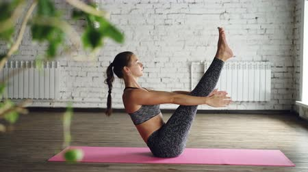 опытный : Side view on young attractive woman practicing boat pose then relaxing in lotus position with hands on knees and breathing. Green plant in foreground, white wall in background. Стоковые видеозаписи