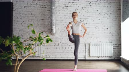 witalność : Starting female yoga student is doing sequence of balance exercises in one-to-one yoga class. She is sometimes awkward but making good progress. Learning yoga concept. Wideo